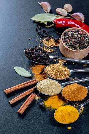 Elf Gewürze auf Löffeln auf schwarzem Hintergrund - Curry, Knoblauch und Kurkumapulver mit Senfkörnern und Berberitzen Zimtstangen, buntem Pfeffer, einer roten Chilischote, Lohrbeerblättern, Knoblauchzehen und Muskatnuss