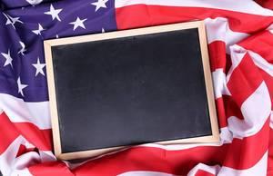 Empty chalkboard on American flag