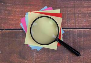 Empty colorful sticky notes with magnifying glass