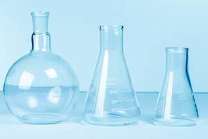 Empty flasks on a light blue background. Laboratory glassware (Flip 2020)