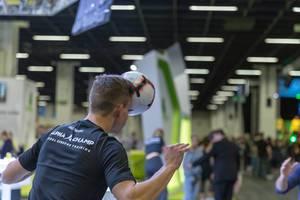 En Sportler von Alpha Champ Lateral Rebound Training träniert mit einem Fußball auf der Fitnessmesse in Köln