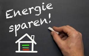 Energie sparen!: Weiße Handschrift mit gezeichnetem Strich-Haus aus Kreide auf schwarzer Tafel - Nahaufnahme