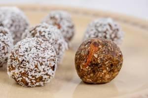 Energiebomben: Kugeln mit Datteln, Kokos und Erdnussbutter auf dem Teller
