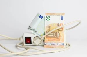 Energiesparkonzept mit Geldscheinen und einem Mehrfachstecker