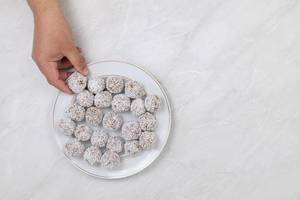 Energy Balls with Coconut in the hand above the table