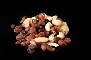 Energy mix with raisins hazelnuts cashew and brazilian nuts above black background (Flip 2019)