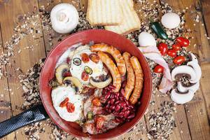 Englisches Frühstück in einer Bratpfanne auf Holzhintergrund