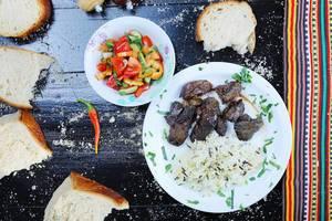 Entenleber mit Wildreis auf einem weißen Teller, mit einer Schüssel Gemüse und Weißbrot vor schwarzem Hintergrund