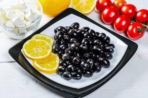 Entkernte schwarze Oliven mit Fetakäse, Tomaten am Strauch und Zitrone appetitlich angerichtet
