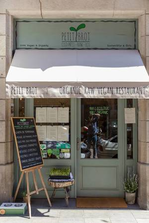 "Entrance of the vegan restaurant ""Petit Brot"" with chalk board in front of a green front door at Carrer del Dr. Dou, near Cathedral of Barcelona, Spain"