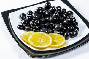 Entsteinte und eingelegte schwarze Oliven mit Zitronenscheiben auf schwarz-weißem Teller