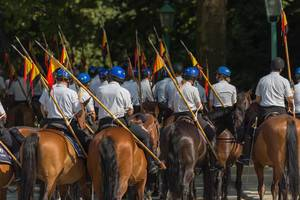 Equestrian police with Belgian flag on their side on a street of Brussels