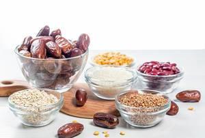 Erbsen, Bohnen, Buchweizen, Hafer, Mehl, Reis und getrocknete Datteln, auf einem weißen Küchentisch