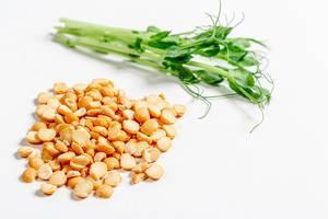 Erbsen-Körner und grüne Erbsensprossen auf einem weißen Hintergrund