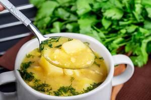 Erbsensuppe mit Kartoffeln und Dill auf einem Löffel und in einer weißen Suppetasse Nahaufnahme