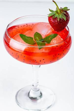 Erdbeercocktail mit Eiswürfeln und Minzblättern im Cocktailglas