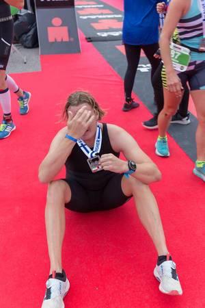 Erfolgreicher Ironman-Teilnehmer des 70.3-Triathlons sitzt erschöpft auf dem roten Teppich und hält seine Medaille hoch