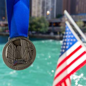 Erinnerung von dem Chicago Marathon am 13.10.2019: Medaille mit blauer Schleife und USA-Fahne und Fluss im Hintergrund