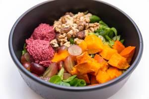 Erntedank Bowl mit Hummus aus roter Beete, Feldsalat, warmer Curry Quinoa, gerösteter Hokkiado Kürbis, rote Trauben, jungem Lauch, Walnusskernen und Joghurt-Orangen-Dip
