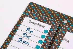 Erstellte Einkaufsliste auf buntem Notizbrett vor weißem Hintergrund
