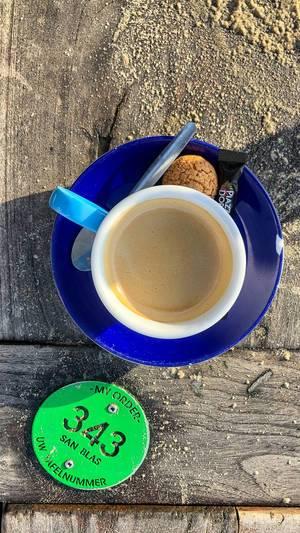 Espresso mit Amaretti und Portionenzucker auf Holztisch neben Plakette mit Tischnummer