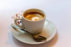 Espresso mit kräftiger Kaffeecrema in weißer Tasse mit Löffel und Zucker