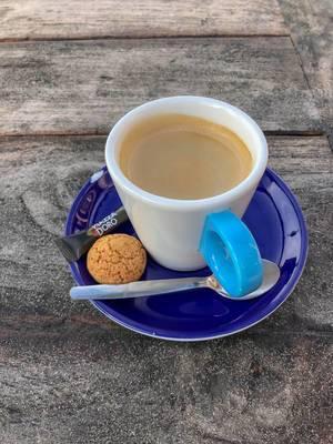 Espresso mit Zucker und Amaretti auf blauer Untertasse auf Holztisch