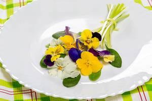 Essbarer Strauß aus Salatblättern und Blüten auf weißem Teller