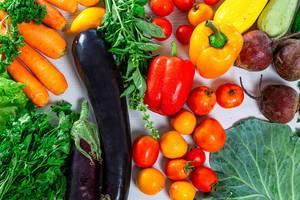 Essenshintergrundbild: Auberginen, Tomaten, Salat, grüne Kräuter und Wurzelgemüse