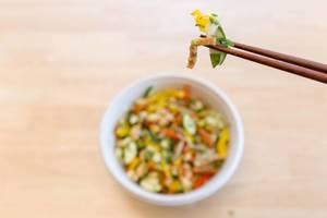 Essstäbchen mit einer Portion Gemüse über veganem Gericht aus Gemüse über Holztisch