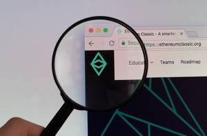 Ethereum Classic logo on a computer screen with a magnifying glass