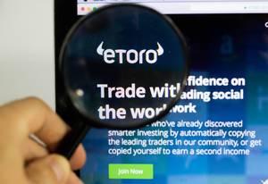 Etoro-Logo am PC-Monitor, durch eine Lupe fotografiert