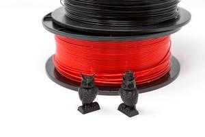 Eulen aus schwarzem Plastik vor PLA-Filament Spulen