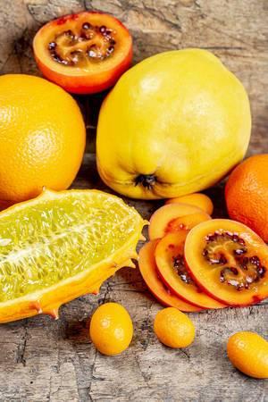 Exotische Früchte wie Kiwano Hornfrucht, Kumquat, Quitte und Tamarillos auf einem Holztisch