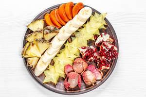 Exotische, reife Früchte in Scheiben geschnitten, auf einem Teller aus der Sicht von oben