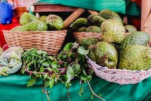Exotisches Obst und Gemüse in Holzkörben verkauft von einem Straßenhändler