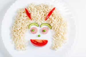 Face made of macaroni, sausage, avocado and tomato slice and green peas on white plate