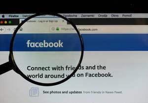Facebook-Logo am PC-Monitor, durch eine Lupe fotografiert