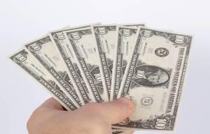 Fächer aus US-Dollar Banknoten gehalten von Hand vor weißem Hintergrund