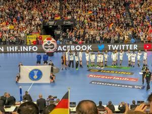 Fahne der International Handball Federation auf Handballfeld vor Deutscher Mannschaft
