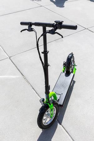 Fahrbereiter elektrischer Tretroller in grün und schwarz, als umweltschonendes Fortbewegungsmittel für Stadtfahrten