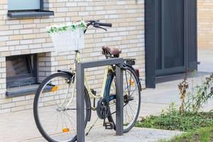 Fahrrad mit Blumen-Deko vor der Haustür angekettet