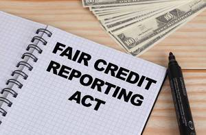 Fair credit reporting act text in notebook and Dollar banknotes on wooden table