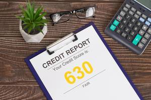 Fair credit score report of 630 on office table