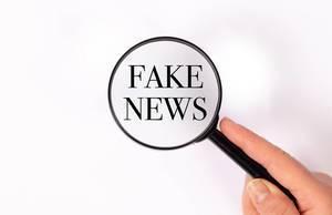 Fake news  unter der Lupe auf weißem Hintergrund