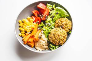 Falafel and vegetables vegan bowl on white background