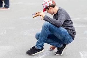 Fan mit gepunkteter Mütze (Bergwertung) malt mit Kreide auf der Straße