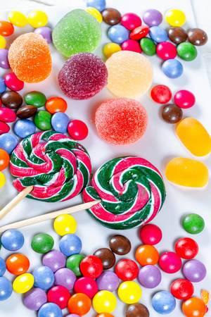 Farbenfrohe Süßigkeiten und zwei Lollipop auf weißem Untergrund