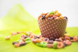 Farbenfrohes Müsli mit einer pink-weiß gepunkteten Snackbox auf grünem Untergrund