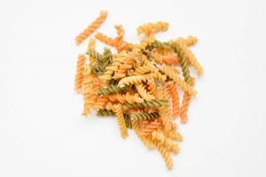 Farbige Fussilli Nudeln Pasta mit weissgrauem HIntergrund